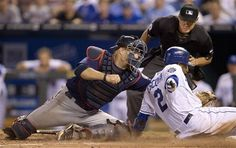 Minnesota Twins catcher Ryan Doumit, left, tags out Kansas City Royals' Alcides Escobar (2) during the eleventh inning of a baseball game at Kauffman Stadium in Kansas City, Mo., Friday, July 20, 2012. Home plate umpire D.J. Reyburn, back, looks to make the call. The Twins defeated the Royals 2-1 in eleven innings.