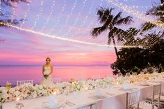 A beautiful fairy light net lighting the table adorned with a runner of fresh flowers and candles