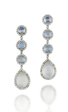 A PAIR OF 18 CARAT WHITE GOLD MOONSTONE AND DIAMOND EAR PENDANTS Each composed of a series of three circular moonstone cabochon and brilliant-cut diamond cluster panels, suspending a similarly designed moonstone and diamond pear shaped drop, London hallmarks for 18 carat gold, 5.8cm long, post fittings
