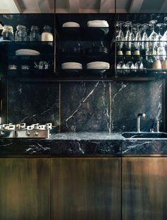 The kitchen is clad in black marble and dark wood, it looks modern and luxurious