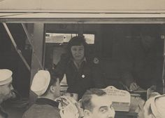 Q57122 - Harriett Engelhardt working inside an American Red Cross Clubmobile. Sailors are in front of the vehicle, waiting to receive the coffee and doughnuts the Clubmobile served. (ADAH)
