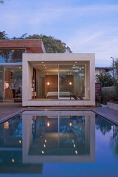 The small portal serves as the bedroom and is perfectly aligned with the water. The sides are solid, and the opening is fully transparent — a sliding glass wall bisected in the middle