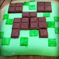 Minecraft Cake. I Think I could do this, only a little neater maybe. I like the idea of using chocolate bars to make the Creeper face.