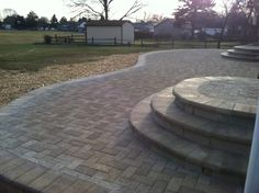 Landscape construction of elevated Hanover Prest brick patio with rounded steps featuring a 90 degree herringbone pattern.