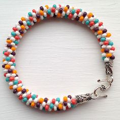 Kumihimo fans, here is a fun and colorful pattern for you. This Burst of Color Kumihimo Bracelet is a fabulous bracelet to make for the summer, or anytime you need a little bit of bold color in your life. Create a beaded kumihimo bracelet. Seed Bead Bracelets, Seed Bead Jewelry, Beaded Jewelry, Jewellery, Seed Beads, Diy Jewelry Projects, Jewelry Crafts, Jewelry Patterns, Bracelet Patterns