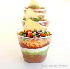 Individual 7 layers dip:  1 (16 ounce) can refried beans  1 (1 ounce) package taco seasoning  1 cup guacamole  1 (8 ounce) container sour cream  1 cup chunky salsa or pico de gallo  1 cup shredded cheddar or Mexican blend cheese  2 Roma tomatoes, diced  1/2 bunch of green onions, sliced  1 (2.25 ounce) can of sliced olives, drained    8 (9 ounce) plastic tumblers  tortilla chips