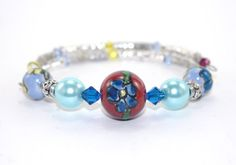 Handcrafted memory wire bracelet is composed of a 16 mm (.63 in) red blue ceramic flower bead, that is enhanced with blue Swarovski crystals and