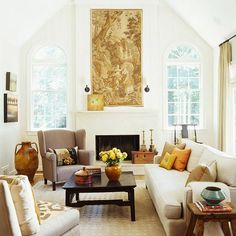 Enlarge Space with White  A narrow living room escapes feeling constrained thanks to white walls, a tall vaulted ceiling, pale floors, bare windows, and white upholstery. A long tapestry on the fireplace wall emphasizes the vertical dimension, while a gray wing chair and espresso brown coffee table ground the space.