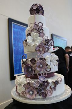 Beautiful #weddingcake with purple flowers & details by Party Flavors from the #ORLPWGShow.