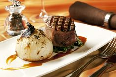 Natural beef tenderloin, featuring horseradish gruyere potato gratin stuffed sweet onion, wilted greens, cabernet jus paired with a glass of wine in a warm and inviting atmosphere.