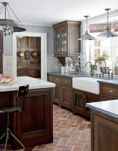 "I like the dark cabinets, farmhouse sink, wall tile, & flooring...Kitchen Workspace:   Some of the lower cabinets have a metal grating instead of wood, to add another layer of texture. ""It reminds me of those old-fashioned pie safes, and it lets things breathe and dry,"" Dan Ruhland says. Parefeuille Peach antique terra-cotta flooring from Exquisite Surfaces."