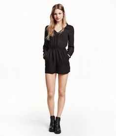 V-neck jumpsuit in woven fabric. Buttons at front, long sleeves with roll-up tab and button, and elasticized seam at waist. Chest pockets and side pockets. Unlined.