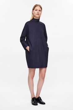 Made from a lightweight denim, this dress has a standing collar that is tied…