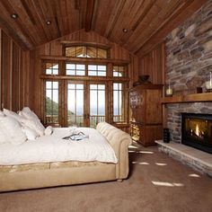 I love the rustic look of this bedroom and the windows and fireplace are perfect.
