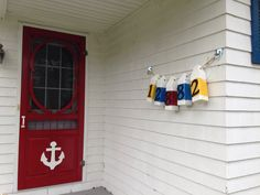 Red screen door with anchor, nautical buoy house number sign. Oceanfront home in Nova Scotia near Peggys Cove