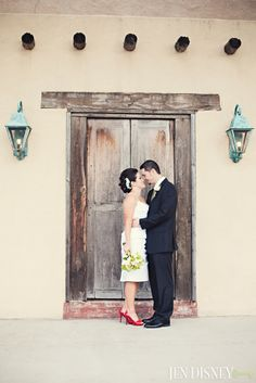 Bride and groom pose in front of a  rustic wooden door and pale blue lanterns. The red shoes on her short and simple dress really standout.