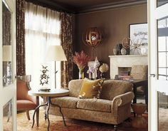 A Barry Dixon Design  In this study, designed by Barry Dixon, a sofa covered in a Nottingham paisley from Quadrille and a Julian Chichester twig table sit atop an antique Oushak rug. The mock crocodile leather desk is from Scalamandré, as is the curtain fabric, Ping.