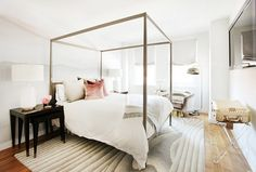 Glam bedroom with a canopy bed, and layers of blush and gray hues