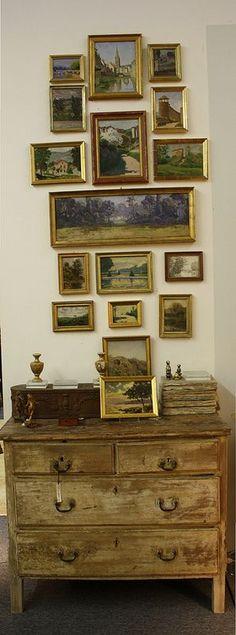 Vintage paintings hung over vintage furniture.