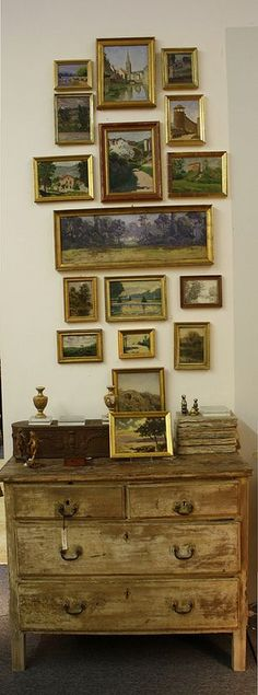 Vintage paintings hung over vintage furniture.