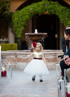 Flower girl for outdoor wedding ceremony with gold sparkle top, white tool skirt, maroon ribbon and large red flower in her hair | About Love Photography | villasiena.cc