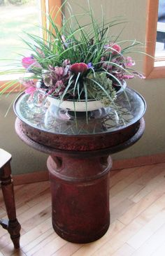 Plant stand made from an old tire rim and milk can...