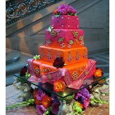 Tiered cake in red, orange, pink and purple layers, maybe ombre, with gold henna pattern