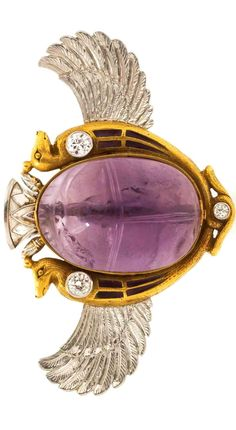 An Egyptian Revival Platinum, Gold, Enamel, Amethyst and Diamond Winged Scarab Brooch, centering on a carved amethyst scarab measuring approximately 20.15 x 14.32 mm within a textured gold setting depicting two stylized creatures accented with translucent purple enamel and three old European cut diamonds weighing approximately 0.24 carat total, accented with intricately textured platinum wings and top. 11.40 dwts.