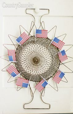 Repurpose a wire egg basket as a metallic wreath, giving it a quick-and-easy patriotic makeover with stick flags. Photography and styling by Matthew Mead. Wire Egg Basket, Country Wall Decor, Mead, God Bless America, Flags, 4th Of July, Dream Catcher, Primitive, Repurposed