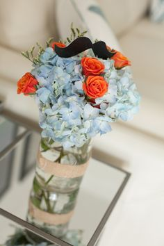 Mustache Baby Shower - we love the floral centerpieces topped with mustaches! #babyshower #mustachebash