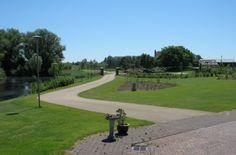 Toegangsweg van bruin asfvalt bij een landelijke tuin