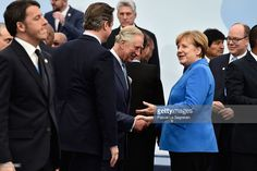 Prince Charles shakes hands with German Chancellor Angela Merkel (R) as Italien Prime Minister Matteo Renzi walks past before the Family photo of the Cop 21 on November 30, 2015 in Paris, France.