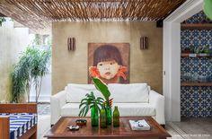 Varanda de casa de praia tem sofá branco, móveis de madeira e pérgola feita com biribas de eucalipto.