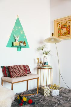 If you got a small space and wanna do something fun this Christmas, because  you think a real Christmas tree is, like, too cheesy, then how about paint  something graphic on the wall? Like a triangle that looks like a Christmas  tree! Check out these fun and clever holiday decorating ideas by Justina  Blakeney. The tufted bench, deer head, grey fur throw, and LED lights are  from Target.  Photographs by me. Sponsored by Target.