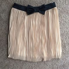 Perfect Neutral Tan and Black Bow Pleated Skirt The most lovely neutral skirt! Tan skirt with tiny pleats and a black satin-y ribbon waist. Has a nice satin-y lining in it and side zip. From Forever 21, size S, true to size. Worn only a couple times, perfect condition. Forever 21 Skirts