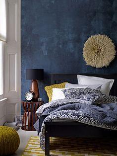 Une chambre dominée par le bleu sombre, mais plein de nuances, et avec des touches de bois foncé et de jaune citron.