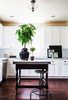 White kitchen with vintage table as an island.