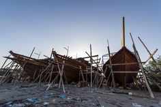 Scaffolding and raw timber planks on the bows of dhows during construction. Sur, Ash Sharqiyah Region, Gulf of Oman, Sultanate of Oman.