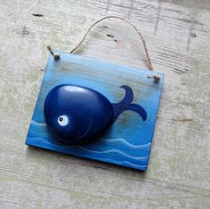 'Whale' - flint - hardwood, painted and stained and is complemented by stone - pebble, hand painted. Pebble forms body of whale, and the rest is painted on.
