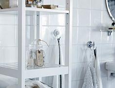 Uma estante de casa de banho em branco com artigos essenciais para visitas, como sabonetes extra e toalhas.