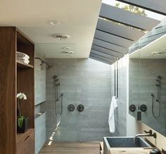 In this modern bathroom, a large skylight keeps the space feeling bright and open, while a glass shower screen separates the two person shower from the rest of the bathroom. The one level wall in shower is simple to enter and exit Modern Master Bathroom, Small Bathroom, Two Person Shower, Architecture Design, 1960s House, Bathroom Wall Decor, Bathroom Ideas, Bathroom Designs, Bathroom Lighting