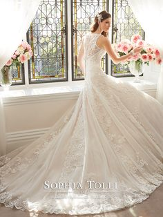 Sophia Tolli - Y11641 – Aricia - Sleeveless Athena tulle A-line wedding gown with lace and tulle shoulder straps, plunging soft V-neckline with modesty panel, lightly hand-beaded lace appliqué bodice with dropped waist, appliqués cascade down skirt, sheer tulle back bodice with lace appliqués and back zipper both trimmed with covered buttons, scalloped lace hem and split back chapel length train.  Sizes: 0 – 28  Colors: Ivory/Pink, Ivory, White