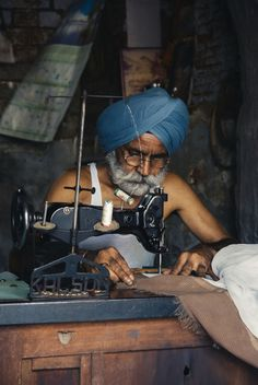 Amritsar, India - June 30, 2008: Old man with blue turban working in his small tailor shop by Alex & Berg