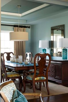 The trey ceiling, crown molding, and classic wood furnishings create an overall traditional feel to this dining room. The grayish blue color palette is accentuated by pops of yellow in the chair upholstery and candle vases.