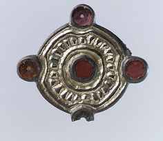 550-600 AD. Whorl-Shaped Brooch Silver-gilt, glass paste, remnant of iron pin Dimensions: Overall: 1 1/4 x 3/8 in. (3.2 x 1 cm). There is a pair of these.