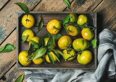 #Fresh Mediterranean tangerines  Fresh green and orange Mediterranean tangerines with leaves in crate over rustic wooden background top view horizontal composition