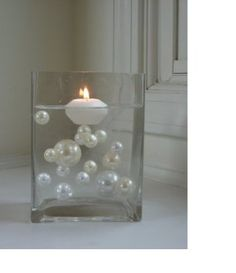 Float oversized pearls in transparent water gels and add floating candles. How simple and pretty would this be for wedding table decor?