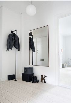 102 Fotos para Renovar seu Hall de Entrada. Espelho retangular, pendente branco, pendurador tubular preto, piso de madeira branca.