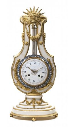 A Louis XVI Style Marble and Gilt Bronze Mounted Mantel Clock   -   of lyre form with a sunburst mask finial over the circular enameled dial with Roman numerals, with jeweled pendulum surround, raised on a stepped oval base, having time and strike movement. Height overall 24 3/4 inches.