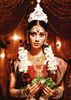 A Bengali bride with traditional gold jewellery, a wire frame gold nath and multiple gold bangles interspersed with red glass bangles.